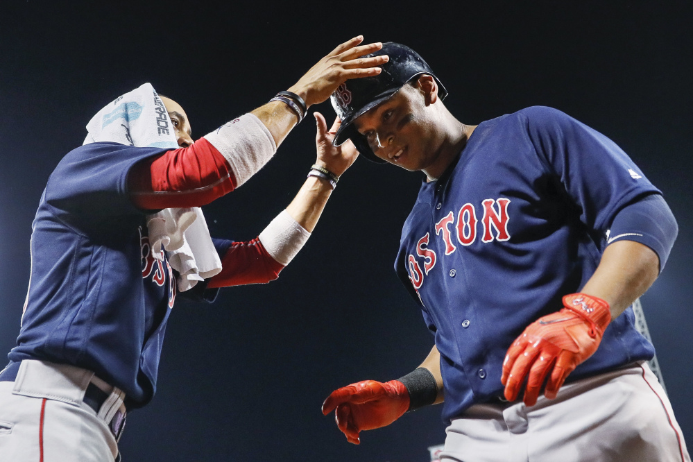 Boston's Mookie Betts, left, takes the helmet from Rafael Devers as they celebrate Devers' three-run home run off Cincinnati Reds starter Sal Romano in the fourth inning Friday night in Cincinnati.