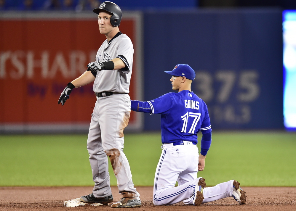 Blue Jays shortstop Ryan Goins holds the tag on Todd Frazier after Frazier hit a double in the third inning at Toronto on Friday. One play later, Goins got Frazier out on a hidden ball trick.