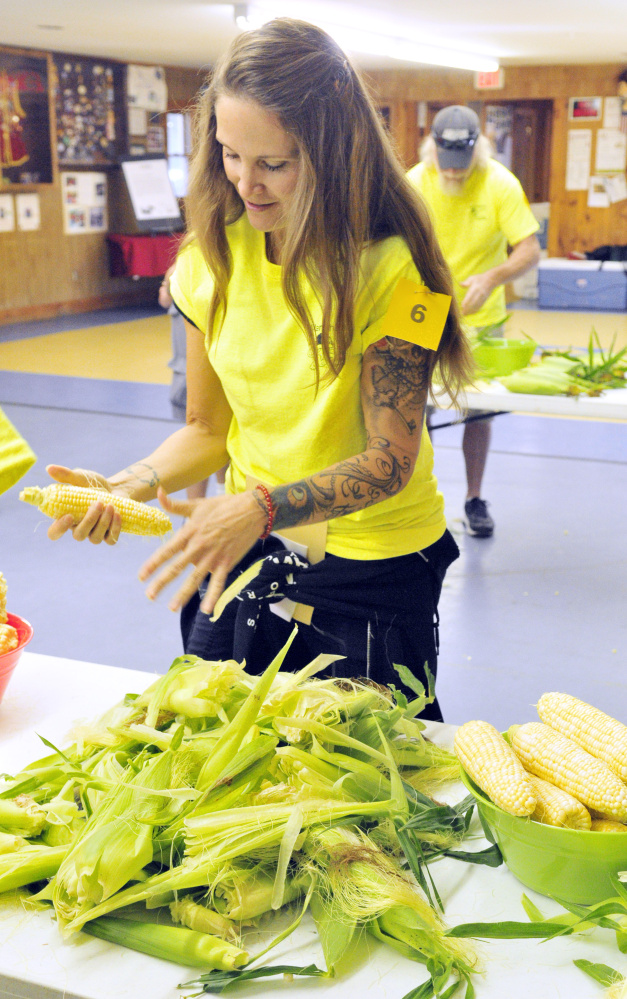 Tina Keech shucks corn in the first event of the Central Maine Amazing Race fundraiser Saturday at the Lions Club in Manchester.