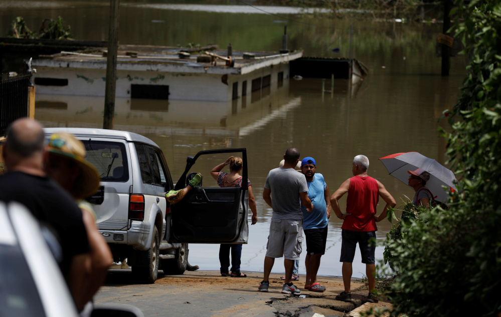 Floodwaters near the roofs of buildings close to Lake Guajataca in northwest Puerto Rico. A dam on the lake was badly damaged by Hurricane Maria and could give way at any moment, officials said Saturday afternoon.