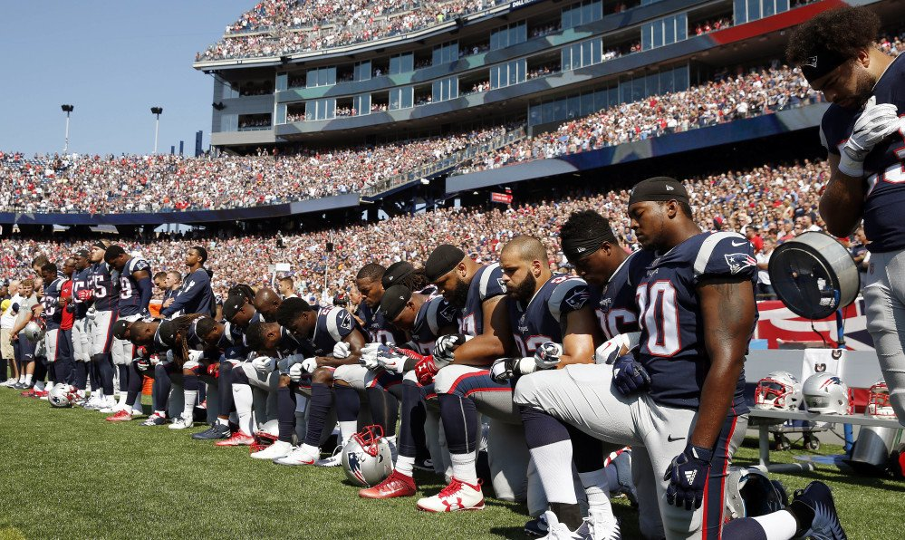 Several New England Patriots players kneel during the national anthem before an NFL game against the Houston Texans on Sunday in Foxborough, Mass.
