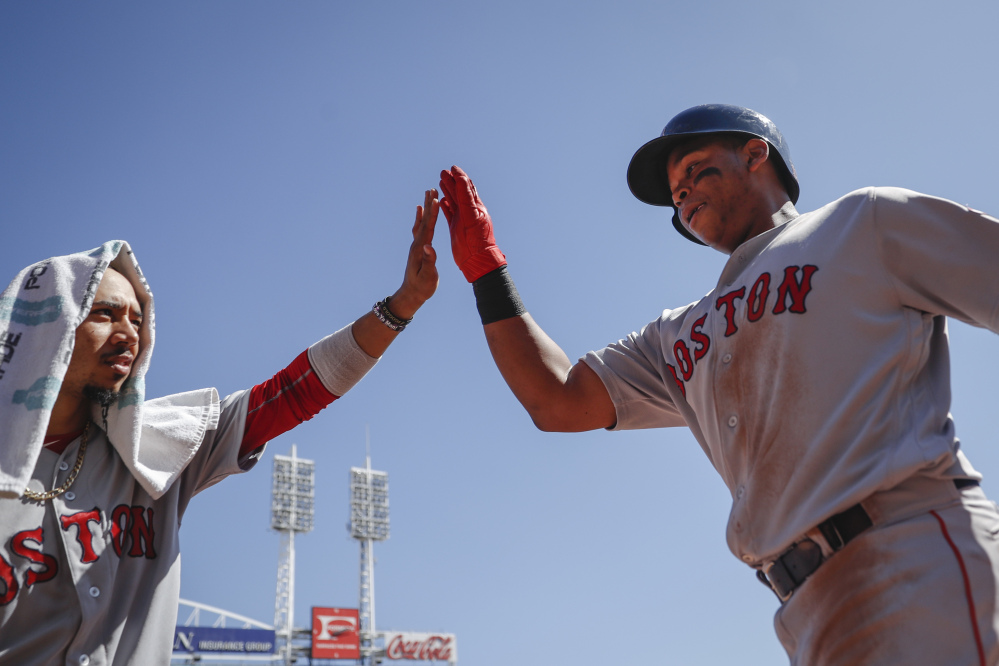 Boston's Rafael Devers, right, celebrates with Mookie Betts, left, after hitting a solo home run off Cincinnati starting pitcher Jackson Stephens in the fifth inning of the Red Sox' 5-4 win Sunday in Cincinnati.