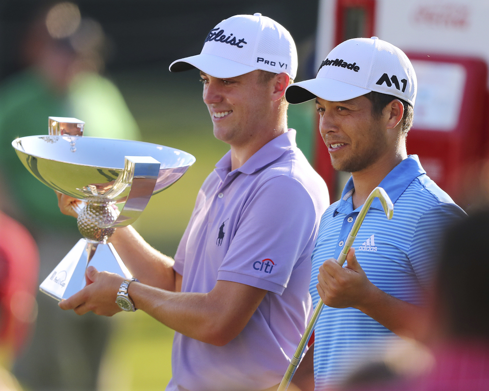 Justin Thomas, left, holds the trophy after winning the Fedex Cup, as he stands with Xander Schauffele who holds the trophy after winning the Tour Championship on Sunday in Atlanta.
