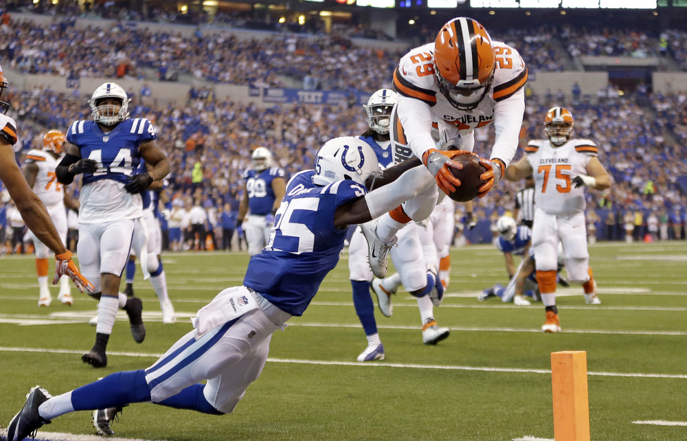Browns running back Duke Johnson dives over Colts defensive back Pierre Desir to score a touchdown Sunday in Indianapolis. Cleveland lost, 31-28.
