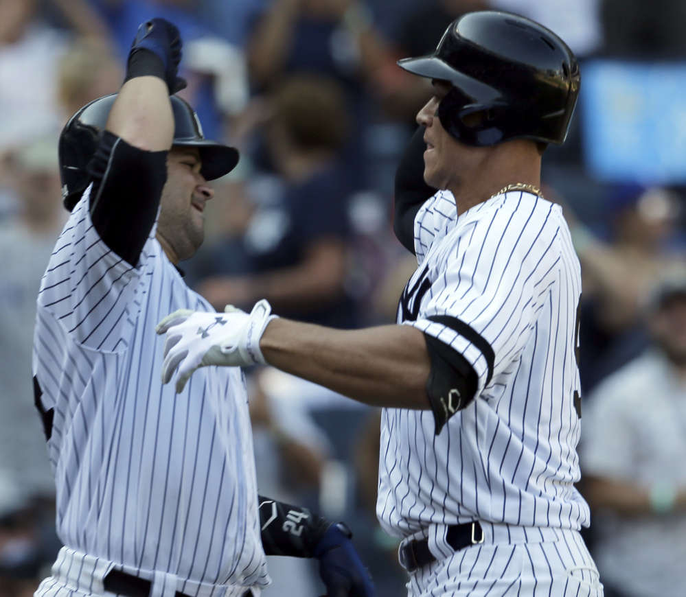 Aaron Judge of the New York Yankees, right, celebrates with teammate Gary Sanchez in the seventh inning after hitting his 50th home run of the season, setting a major league record for homers by a rookie. The Yankees defeated the Kansas City Royals, 11-3.