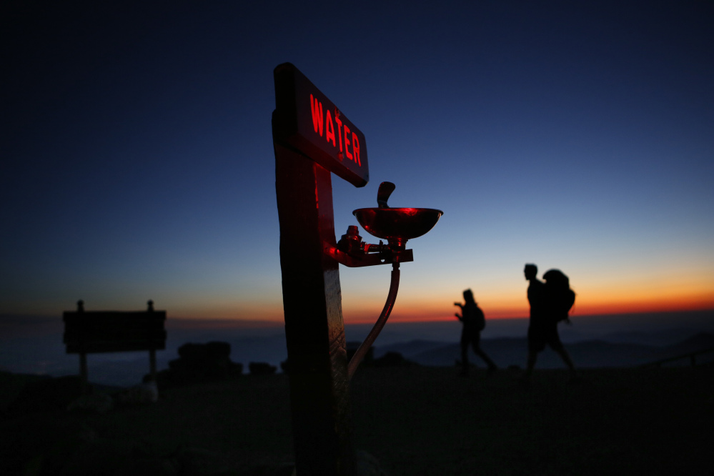 Quincy Andrews, left, and Josh Fournier, both of Meredith, N.H., arrive at dawn Sunday at the summit of Mount Washington, N.H., where a water fountain awaits visitors to New England's highest peak. The weather observatory on the summit recorded a record daily temperature high Sunday when the mercury hit 65 degrees, the highest ever for a Sept. 24.