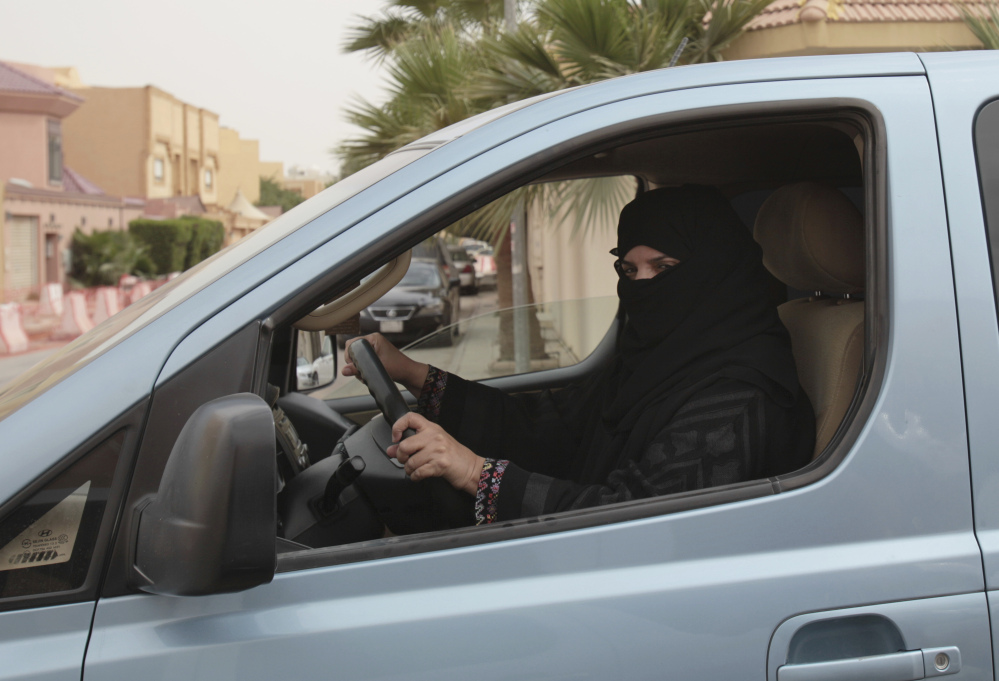 A woman drives a car in Riyadh as part of a 2014 campaign to defy Saudi Arabia's ban on women driving. The kingdom said Tuesday that women can drive starting next summer.