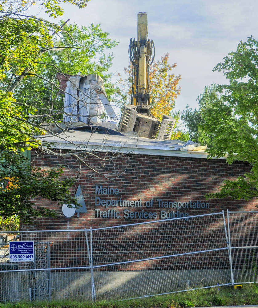 An excavator rips apart the old state DOT building on Sewall Street in Augusta on Friday to make way for a new building to house Maine Public Employees Retirement System offices.