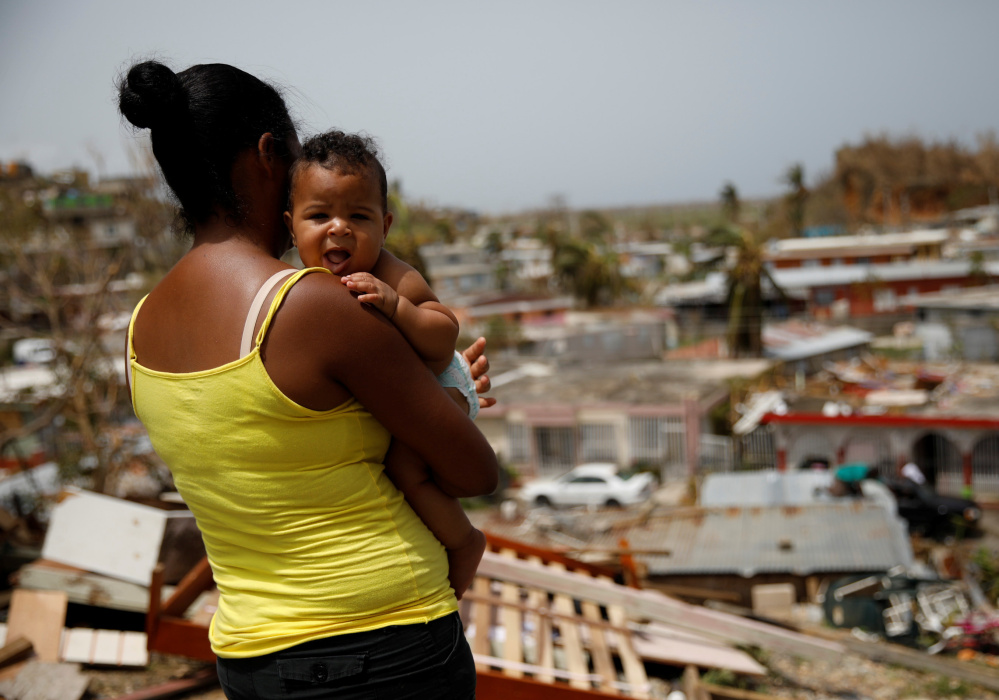 Ysamar Figueroa, carrying her son Saniel, looks at the damage in Canovanas, Puerto Rico, on Tuesday, after the area was hit by Hurricane Maria.