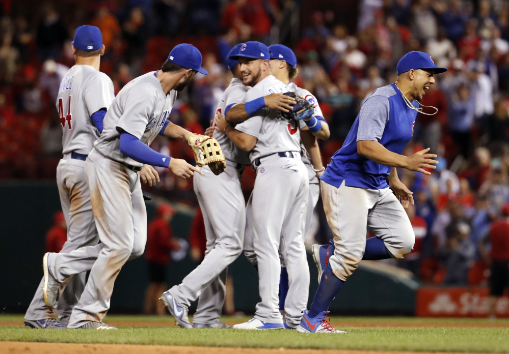 Cubs players celebrate after they defeated the Cardinals 5-1 on Wednesday night in St. Louis to clinch the National League Central title.