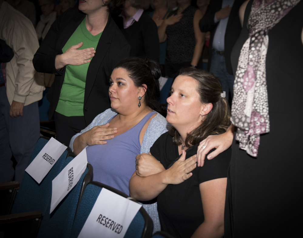 April Fournier, left, and Liz Smith kneel while reciting the Pledge of Allegiance at the opening of a Democratic gubernatorial candidates' forum Thursday evening at the University of Maine at Augusta. Zak Ringelstein led the Pledge of Allegiance and invited attendees to stand or kneel.