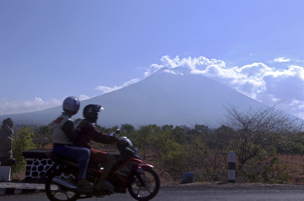 Motorists pass Mount Agung volcano in Karangasem, on the island of Bali, Indonesia. Warnings of an eruption have sparked an exodus of more than 140,000 people.