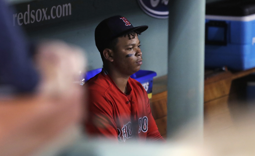 Boston's Rafael Devers sits in the dugout after grounding out to end the game Friday, leaving the Red Sox needing one more win or a Yankees loss to win the AL East.