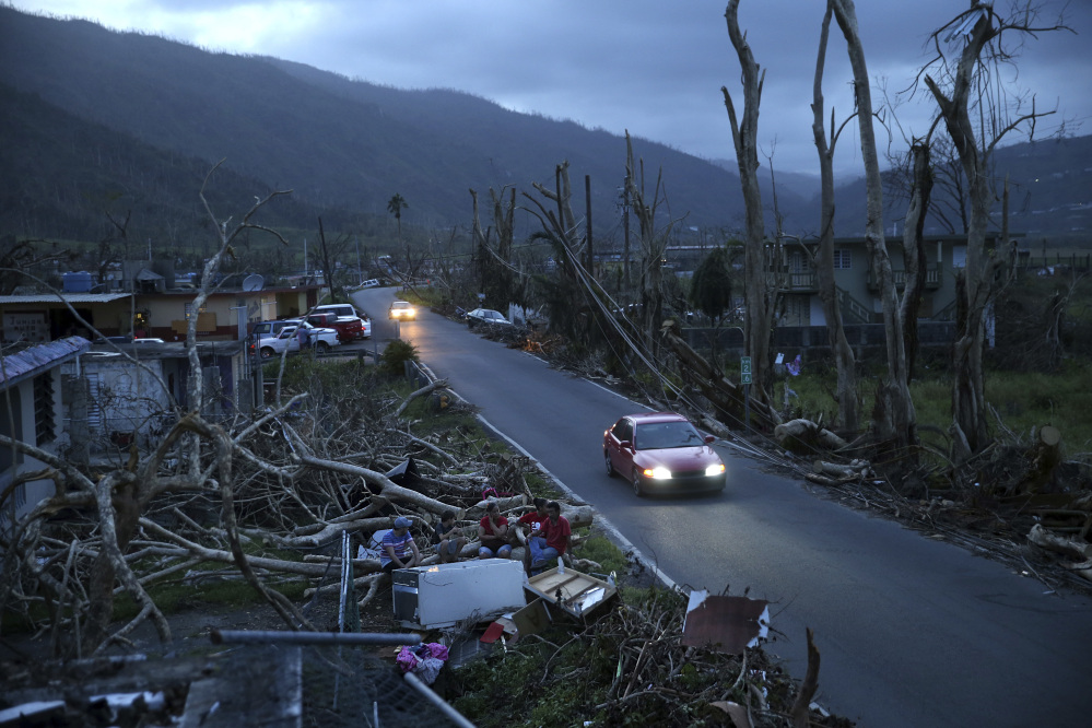 In this Sept. 26 photo, neighbors sit on a couch outside their destroyed homes as sun sets in the aftermath of Hurricane Maria, in Yabucoa, Puerto Rico. A Maine woman who has family on the island has organized a restaurant fundraiser to provide relief to island inhabitants.