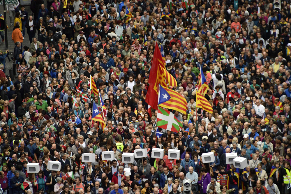Pro-independence supporters carrying mock ballot boxes and Catalan flags, center top, with Basque flags, center bottom, rally in support of Catalonia's secession referendum in Bilbao, northern Spain, on Saturday. Catalonia's planned referendum on secession is due to be held Sunday by the pro-independence Catalan government, but Spain's government calls the vote illegal because it violates the constitution, and the country's Constitutional Court has ordered it suspended.