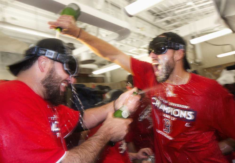 Boston's Matt Barnes, right, celebrates in the clubhouse with teammates after they defeated the Houston Astros 6-3 to clinch the American League East title in Boston on Saturday.