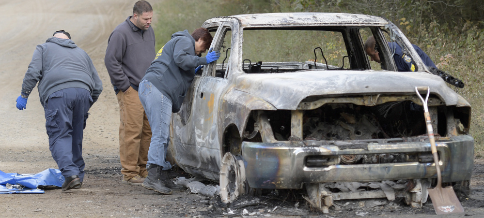 Investigators examine a charred pickup truck containing a body Saturday on Lincoln Street in Richmond.