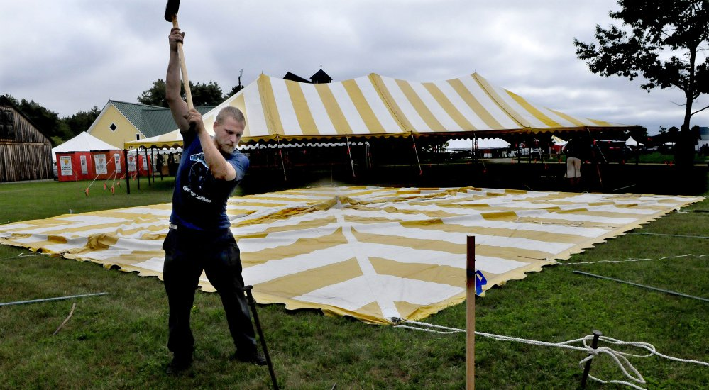 Ryan Childs of Maine Bay Canvas hammers a spike to hold down one of 62 tents that were being erected for the Maine Organic Farmers and Gardeners Association 41st annual Common Ground Country Fair in Unity on Monday. The fair runs this Friday through September 24.