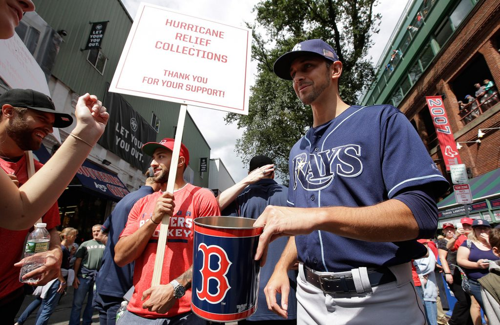 Florida Panthers' Vincent Trocheck, center left, holds a sign as he Tampa Bay Rays' Steve Cishek, right, collect donations outside Fenway Park in Boston for relief efforts after Hurricane Irma, before a baseball game between the Rays and the Boston Red Sox on Sunday in Boston.