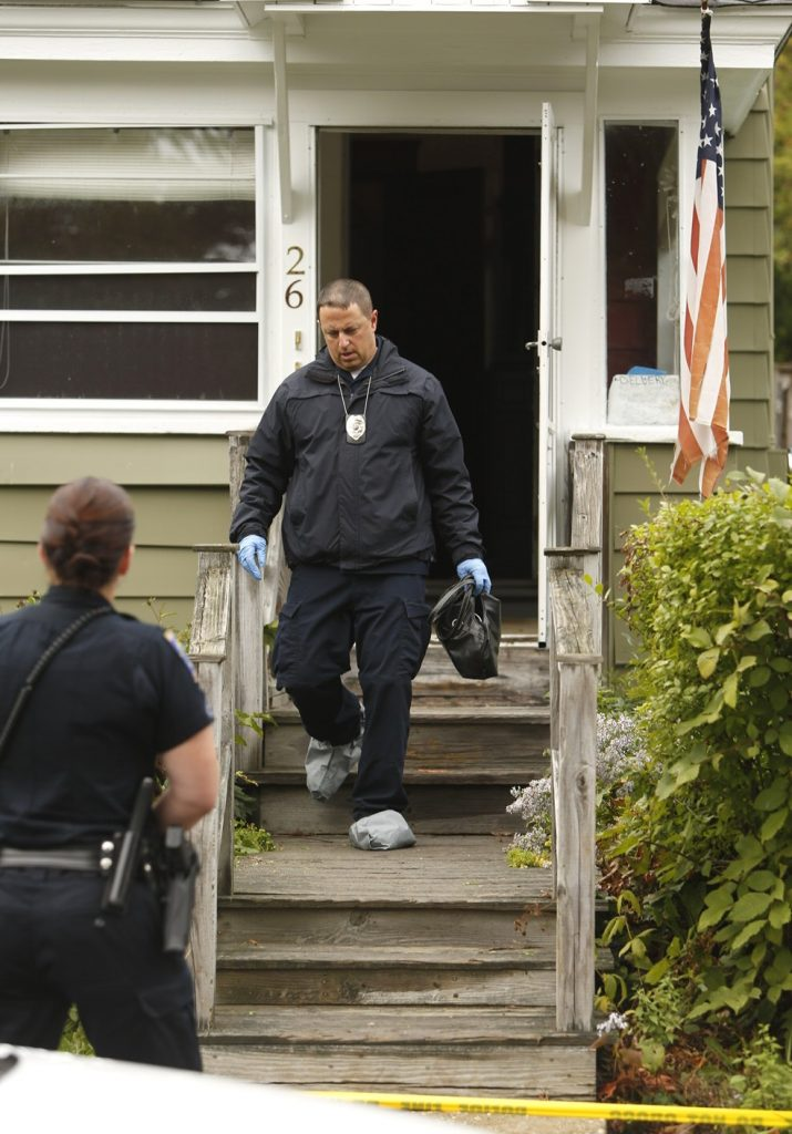 A police investigator exits the front door of 26 Nye St. in Saco.