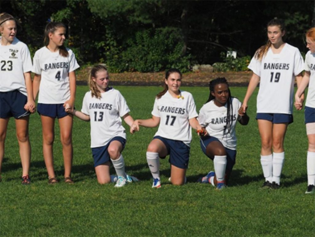 Members of the girls' soccer team at Traip Academy in Kittery take a knee during the playing of the national anthem Monday night.