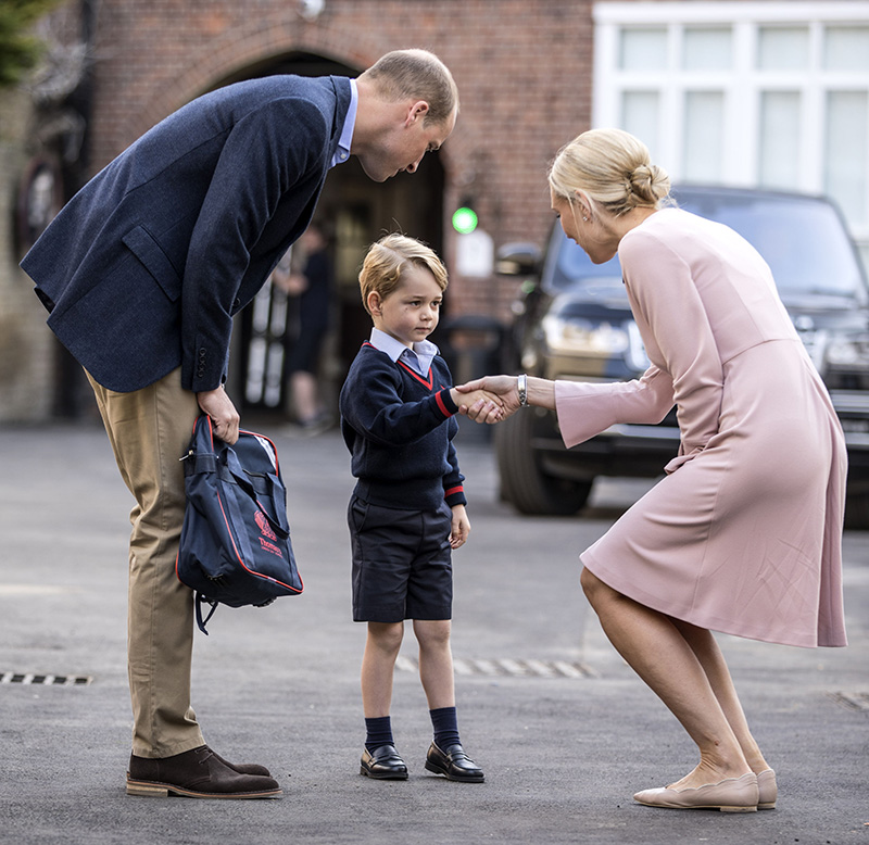 Prince William accompanies Prince George as he is greeted by the head of the lower school as he arrives for his first day of school in  London on Thursday.