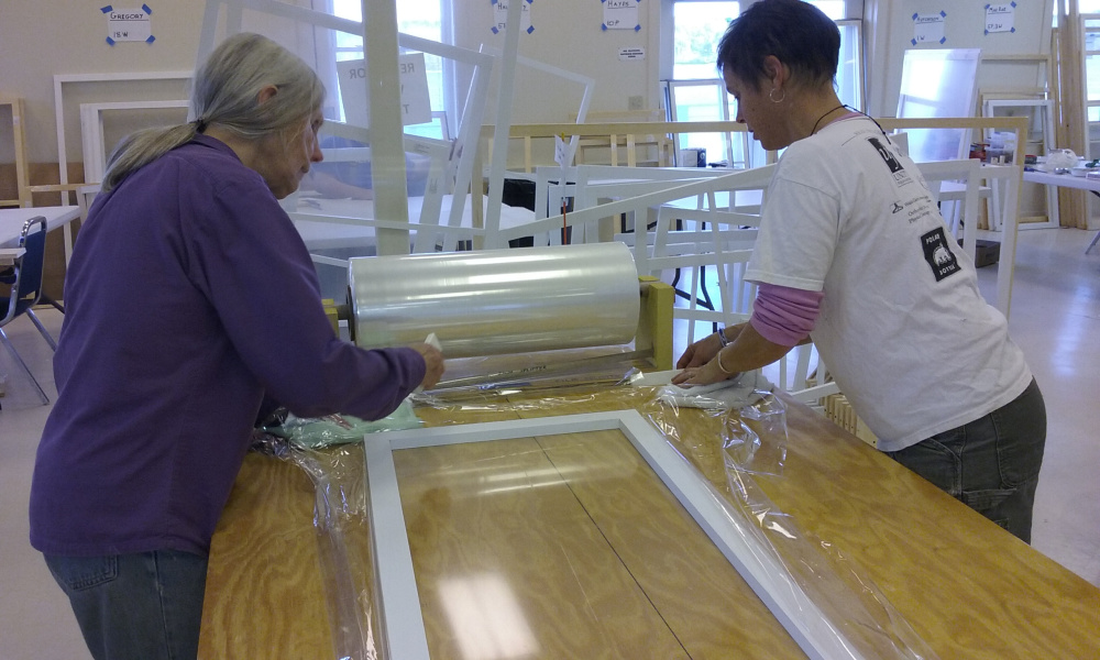 Barbara Kile and Liza Wheeler work with plastic and foam weather stripping to create an insulated window insert.