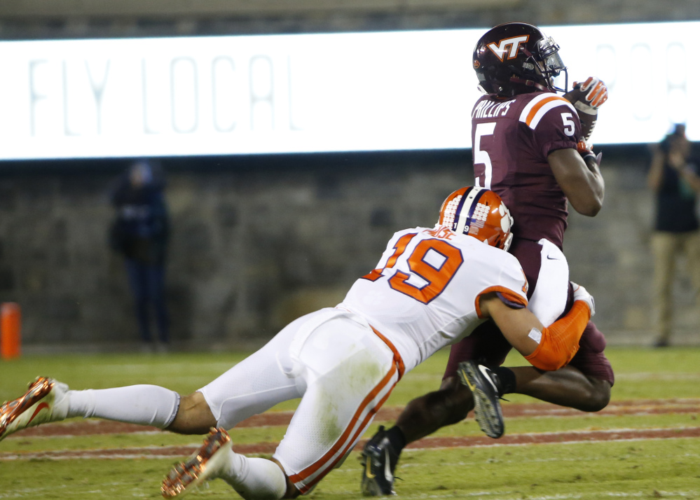 Virginia Tech receiver Cam Phillips hauls in a pass as Clemson safety Tanner Muse makes the stop.