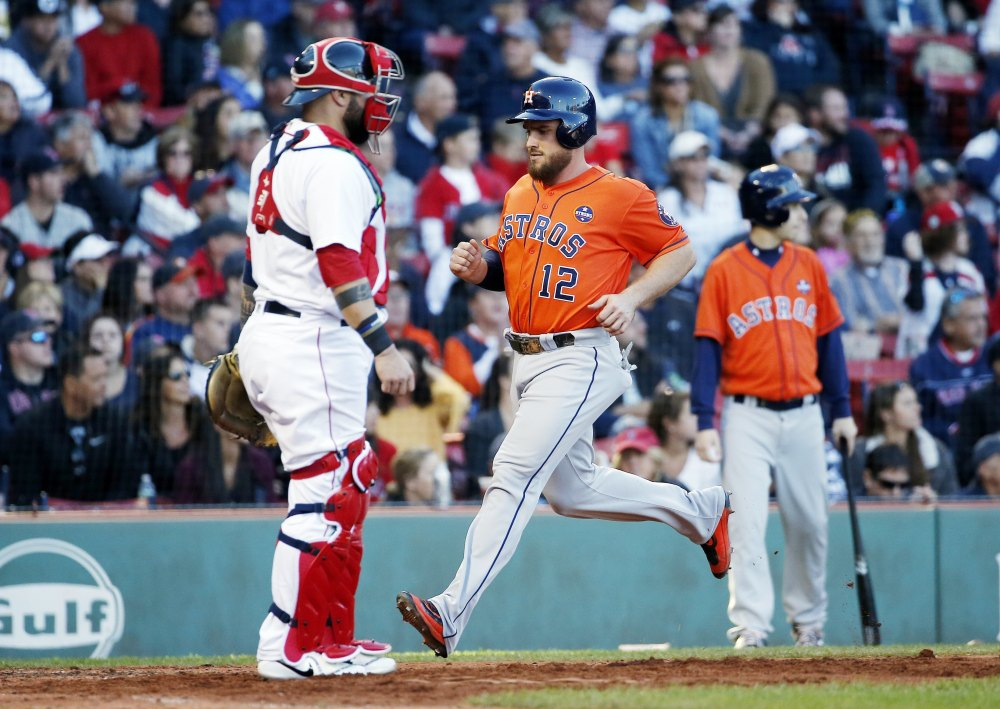 Houston's Max Stassi scores in front of Boston's Sandy Leon in the seventh inning when the Astros scored four times to beat the Red Sox 4-3 on Sunday in Boston.