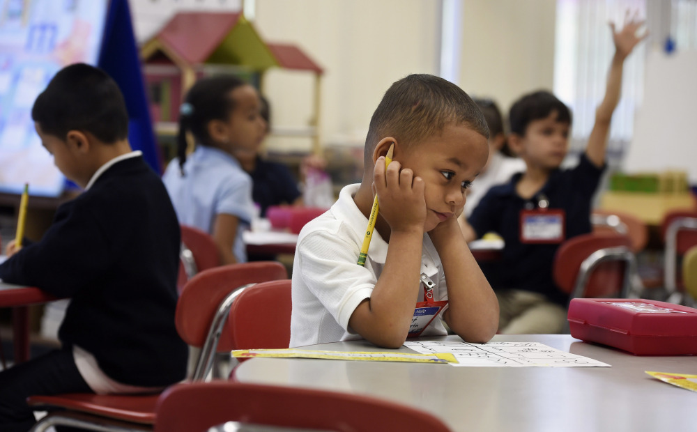 Elionet Saez Martin of Puerto Rico works at his desk in his class at Chamberlain Elementary School in New Britain, Conn., on Friday. His mother put him and his 9-year-old brother, Eliot, on a plane to be with their grandfather.