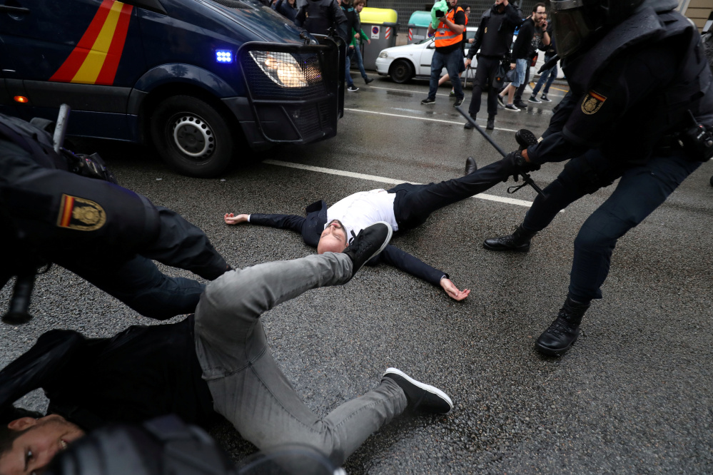 Spanish Civil Guard officers remove demonstrators outside a polling station for the banned independence referendum in Barcelona on Sunday.