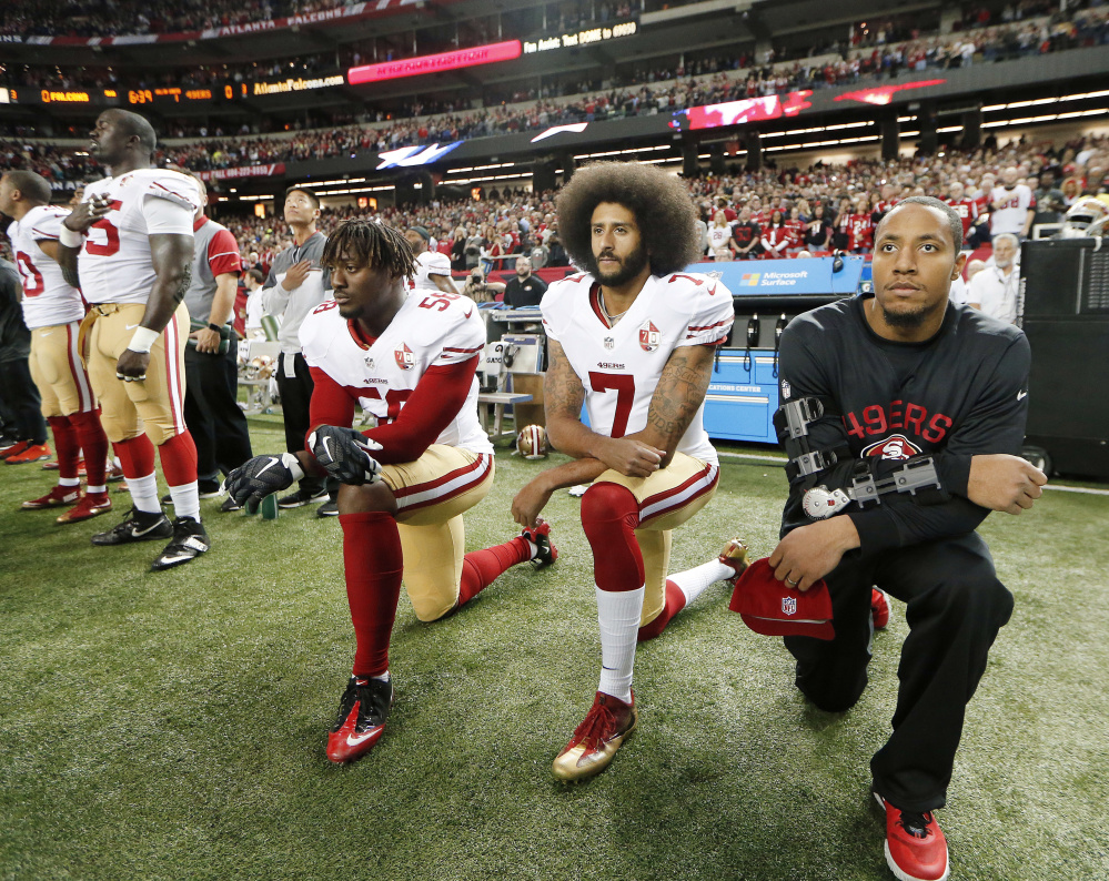 Last season, San Francisco quarterback Colin Kaepernick, center, and linebacker Eli Harold, left, kneeled to protest racial inequality. That message may have been largely lost.