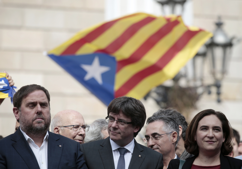 From left, Catalan regional Vice-President Oriol Junqueras, Catalan President Carles Puigdemont and Barcelona Mayor Ada Colau observe a protest called by pro-independence activists in Barcelona, Spain, on Monday. Catalonians voted Sunday in favor of independence.
