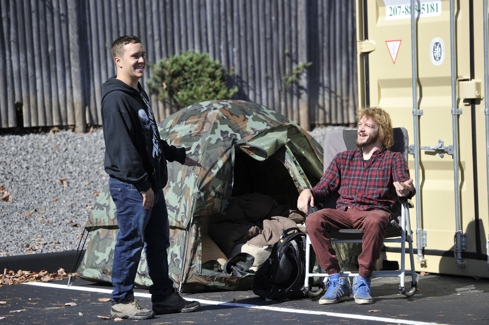 Dave Sirois, left, and Matthew Scally, both of Saco, talk while waiting in the parking lot Monday for Tuesday's Krispy Kreme grand opening. The two were fifth and sixth in line and brought a tent to sleep in overnight Monday.