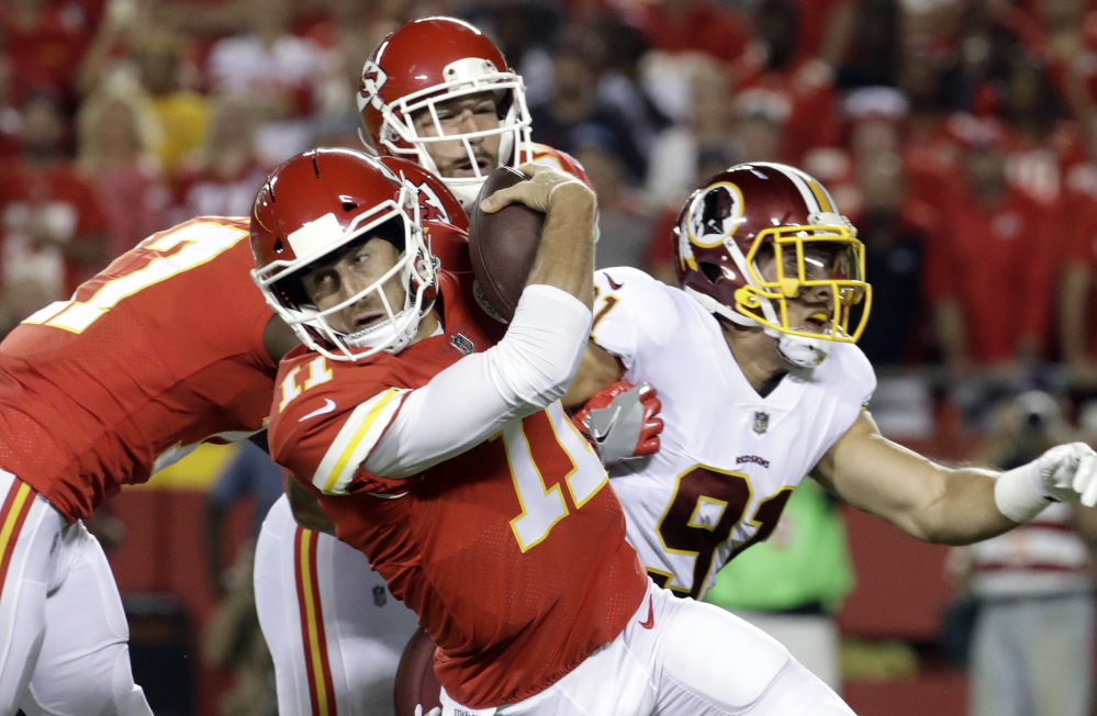 Quarterback Alex Smith of Kansas City attempts to avoid Washington's Ryan Kerrigan, right, during the first half Monday night at Kansas City, Mo. The Chiefs won, 29-20.
