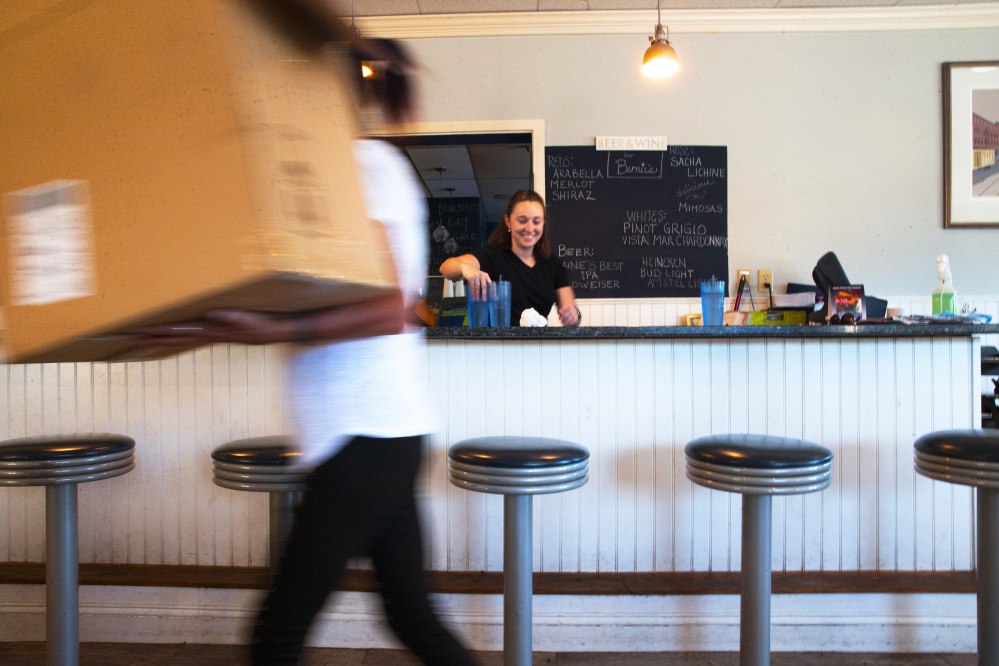 Chantel Ruby, a server at Bernie's Foreside, center, cleans a countertop at the Falmouth diner as Christy Stegner hauls in a box of table decorations for the evening, when the space is transformed into Esidore's Bistro, where Stegner is front-of-house manager.