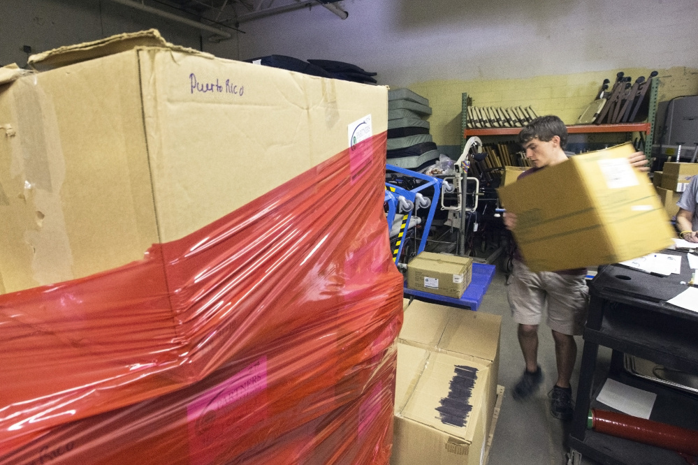 Doug Beahm, an intern for Partners for World Health, loads boxes of medical supplies onto a pallet.