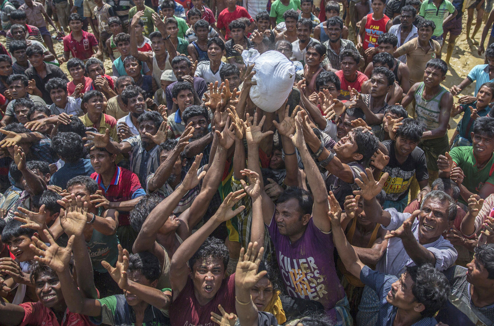 Rohingya Muslims, who crossed over from Myanmar into Bangladesh, stretch their arms out to catch a bag of rice thrown to them during distribution of aid near Balukhali refugee camp. With Rohingya refugees still flooding across the border from Myanmar, those packed into camps and makeshift settlements in Bangladesh are desperate for scant basic resources and fights erupt over food and water.