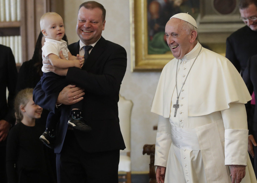 Pope Francis smiles with Prime Minister of Lithuania Saulius Skvernelis, carrying his son Tadas, at the end of their private audience at the Vatican on Friday.