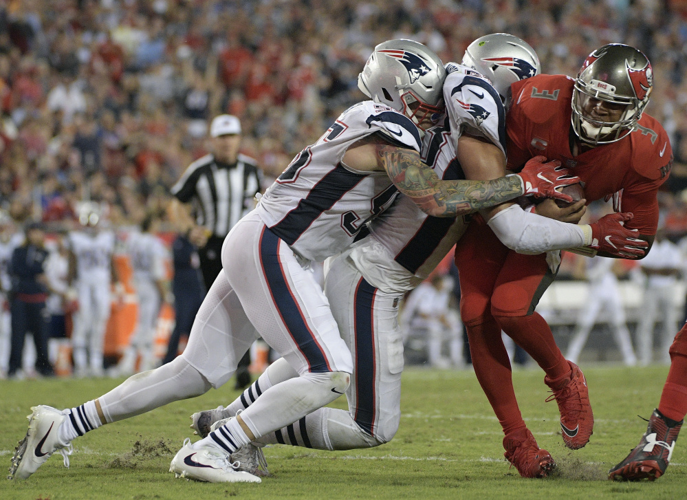 Buccaneers quarterback Jameis Winston, right, is hit by New England defenders in the fourth quarter Thursday night at Tampa, Fla. The Patriots won 19-14 but allowed 300-plus yards passing for the fifth straight game.