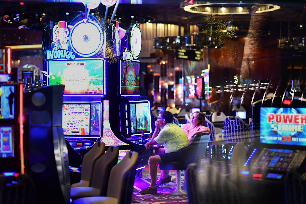 As seen from the sidewalk, gamblers sit at slot machines at Aria Resort and Casino on Tuesday in Las Vegas. Paddock favored high-dollar machines, separated from the rest of casinos, where top players rely on mathematical strategy to shrug off losses while playing for a big payoff.