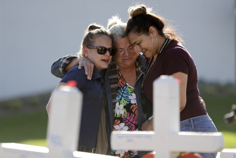 Melissa Gerber, left, Nancy Hardy, center, and Sandra Serralde, all of Las Vegas, embrace Friday as they look on crosses in honor of those killed in the mass shooting Sunday. Investigators still don't know why Stephen Paddock opened fire on thousands of people at the Route 91 Harvest Festival.