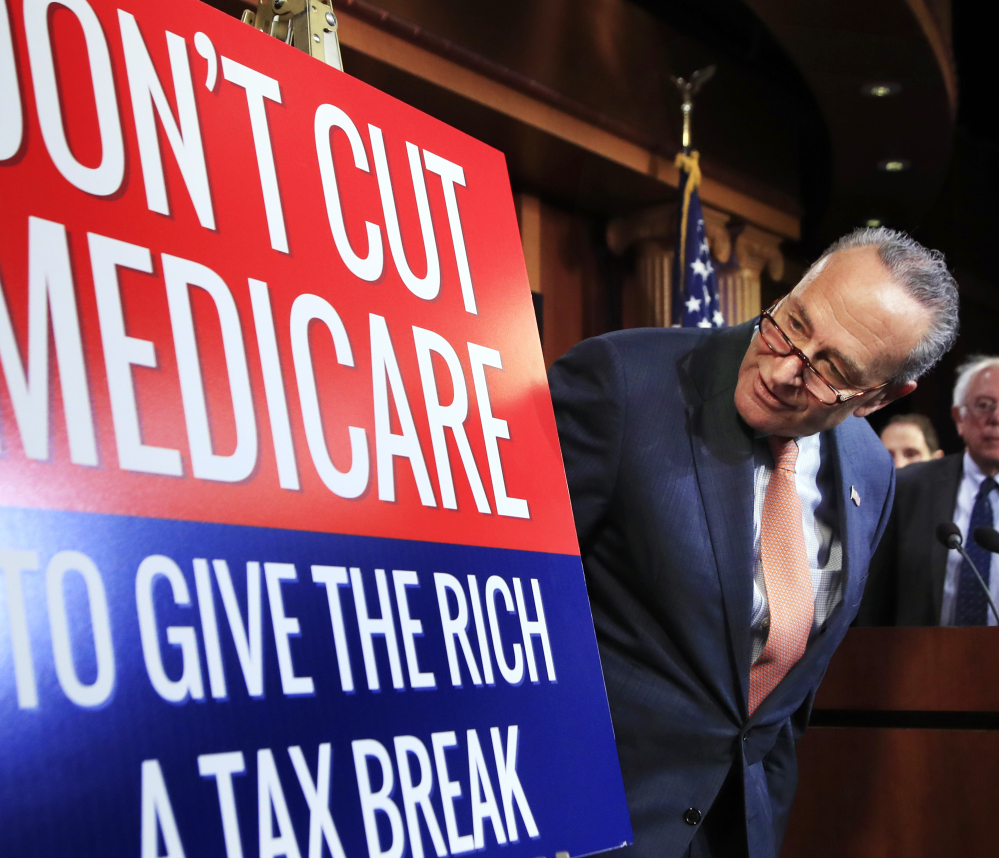 Senate Minority Leader Chuck Schumer of New York looks at a poster at the start of a news conference on Capitol Hill.