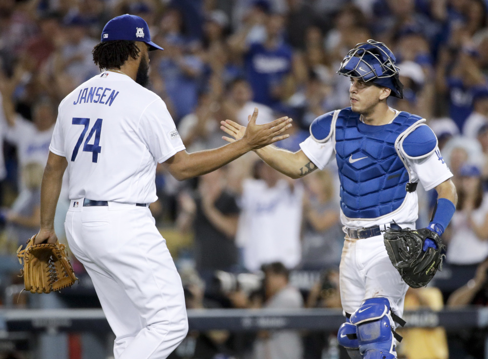 Dodgers catcher Austin Barnes and relief pitcher Kenley Jansen celebrate after their win against the Diamondbacks.