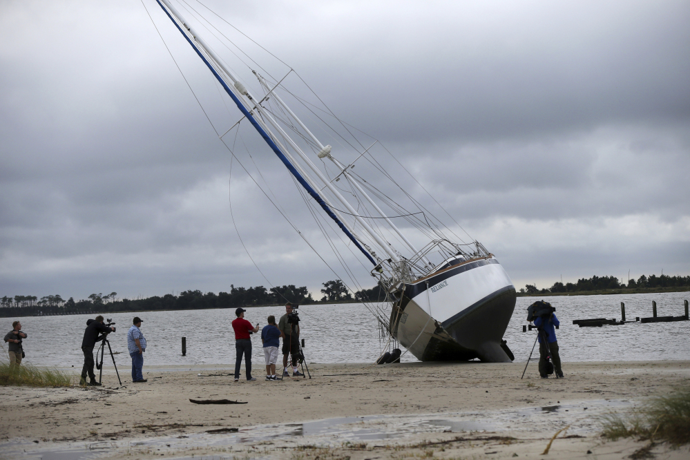 News crews film a sailboat that washed ashore along the Gulf of Mexico in Biloxi, Miss., in the aftermath of Hurricane Nate on Sunday.