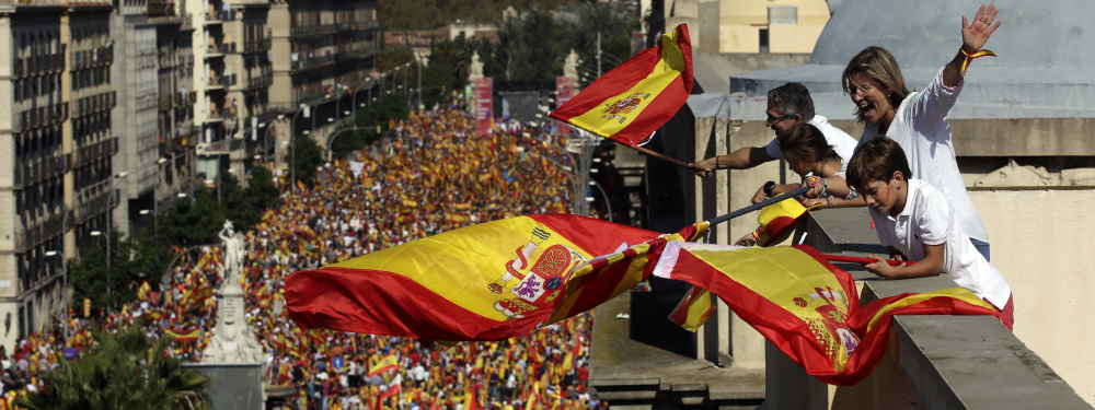 People on a rooftop wave Spanish flags during a march in downtown Barcelona, Spain.
