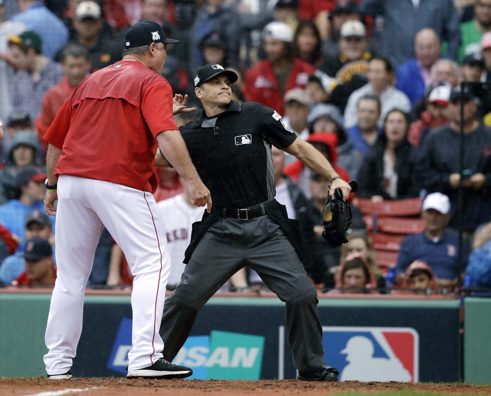 Home plate umpire Mark Wegner ejects Boston manager John Farrell, left, during the second inning Monday in Boston.