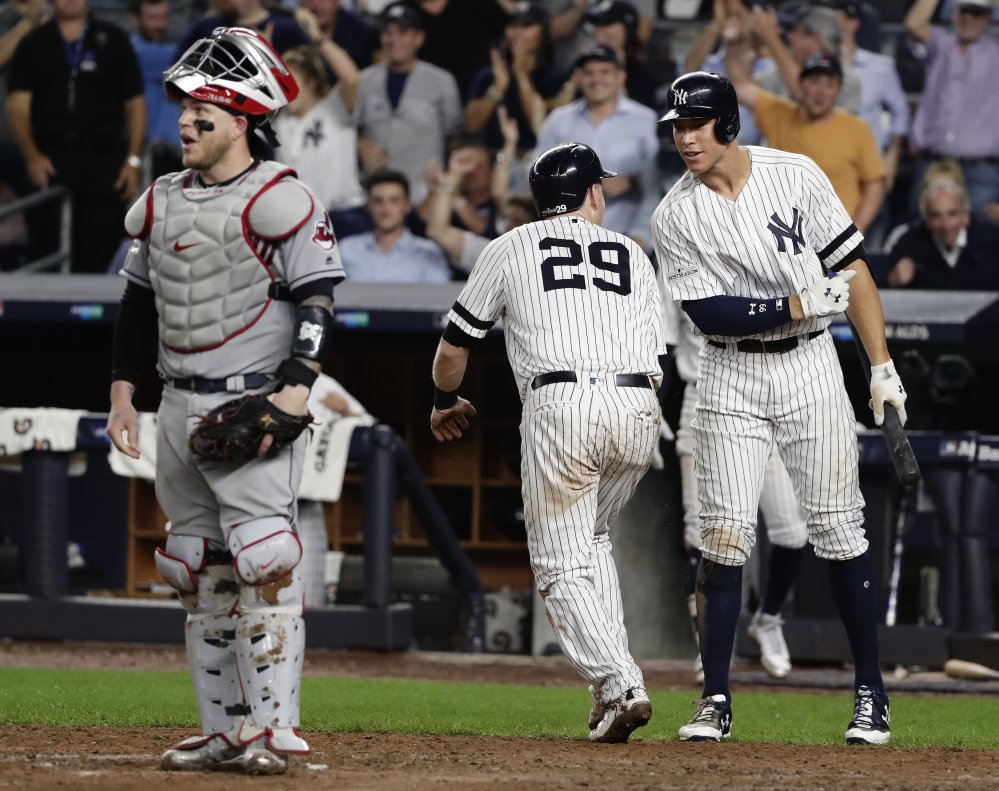 The Yankees' Aaron Judge, right, greets Todd Frazier after Frazier scored from third on a sacrifice fly by Brett Gardner in the fifth inning as New York stretches its lead to 6-3.
