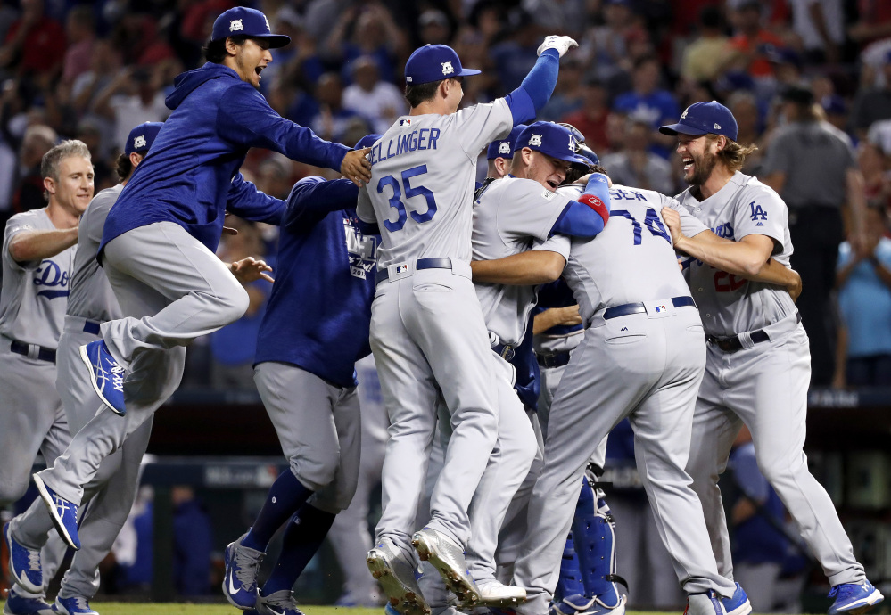 The Dodgers celebrate Monday night after sweeping the Diamondbacks in the NL division series with a 3-1 win. The Dodgers advance to the NLCS and will meet either Washington or Chicago.