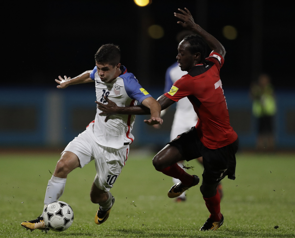 Christian Pulisic of the U.S., left, battles for the ball with Trinidad and Tobago's Nathan Lewis in Tuesday's game in Couva, Trinidad. The U.S. lost 2-1.